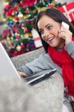 smiling happy woman using using laptop and cell phone on Christm