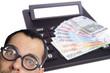Mann mit Brille und Taschenrechner mit Geldscheinen