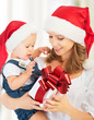 happy family mother and baby with gift  in Christmas hats