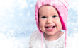 happy baby girl in winter hat smiling on outdoors