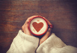 woman holding hot cup of coffee, with heart shape - 57146674