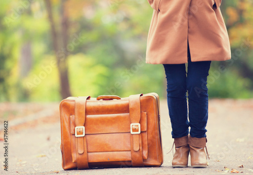 Women's foots near suitcase at autumn outdoor.