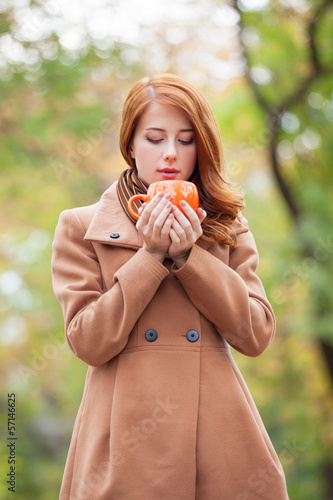 Redhead girl with cup in the park