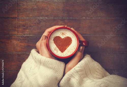 Foto op Canvas Koffie woman holding hot cup of coffee, with heart shape