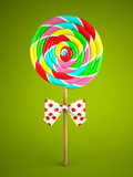 Reainbow lollipop with bow on green background