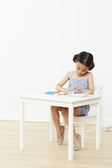 Young girl at table playing with beads