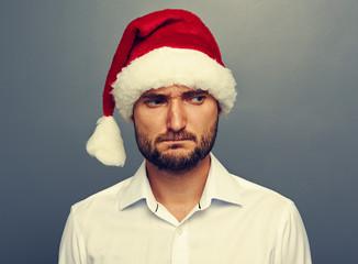 sad man in santa hat over dark