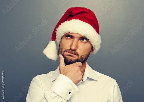 thoughtful man in christmas hat looking up
