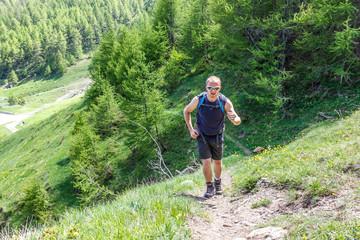 Ragazzo corre su sentiero in montagna