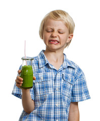 Boy pulling face holding green smoothie