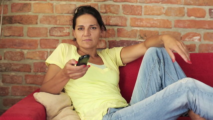Young woman changing channels with the remote control