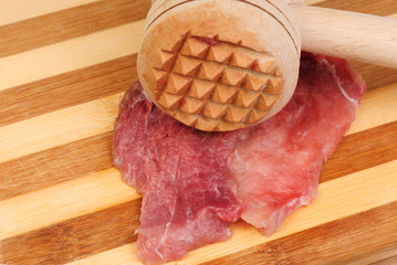 a wooden hammer for beating the meat