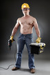 Topless worker holding a drill and a toolbox