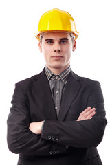Young engineer with arms folded wearing helmet