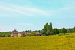 Meadow with big old farm and trees and blue sky. Countryside. Zu