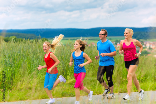 Happy Family is running outdoors in summer