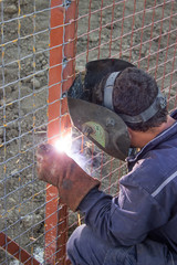 Welder working on installation a metal fence 5