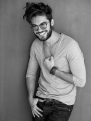 sexy man with beard dressed casual smiling against wall