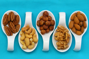 Selection of nuts on porcelain spoons on blue background