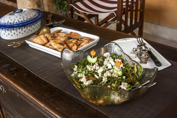 Rustic table with grilled salmon, salad and sauteed potatoes