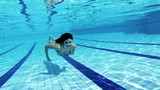 Smiling woman swimming underwater slow motion