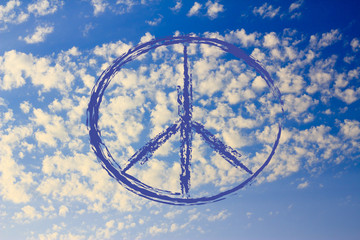 peace symbol on serene blue sky with tiny clouds