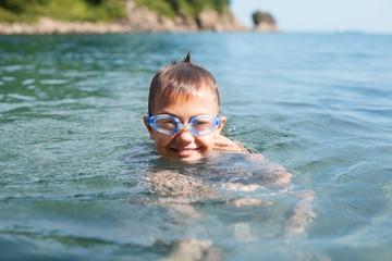 Joyful boy swims in the sea
