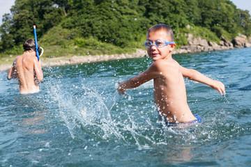 Boy creates large splashes in the sea.