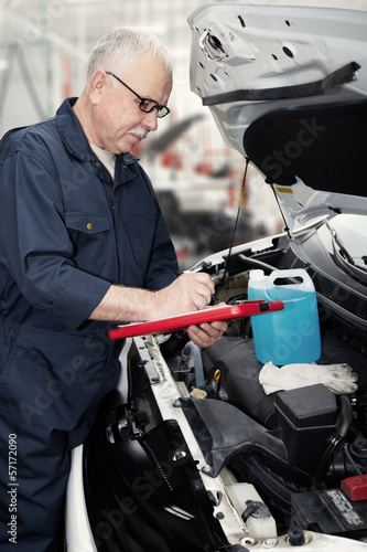 Auto mechanic checking engine.