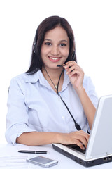 Smiling young Indian call centre woman with headset