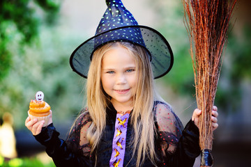 Little girl wearing witch costume eat cupcake on Halloween