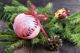 Red Christmas ball with fir tree branch on wooden background
