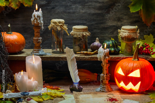 Pumpkin, old scrolls and candles in witch's cottage