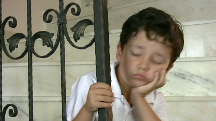 Unhappy little boy sits on old staircase