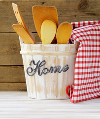 Wooden kitchen utensils on a wooden background