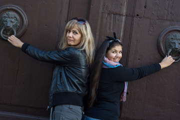 Two women knocking on the door with knockers