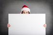 Christmas woman holding white billboard isolated on grey backgro