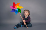 Young kid portrait with windmill over grey background.