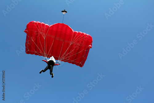 parachutist with red parachute on blue sky