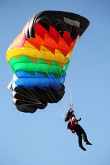 parachutist with colorful parachute on blue sky
