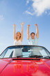 Cheerful couple standing in red cabriolet
