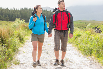 Hikers with backpacks holding hands and walking