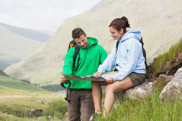 Couple resting after hiking uphill and looking at map