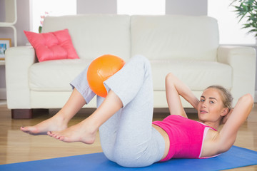Sporty happy blonde doing sit ups holding ball between knees