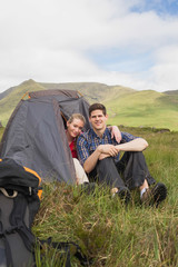 Happy couple sitting in their tent after a hike and looking at c