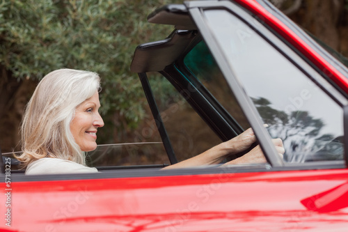 Happy mature woman driving red convertible