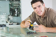 Handsome smiling computer engineer repairing hardware with plier