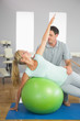 Smiling physiotherapist correcting patient doing exercise on exe