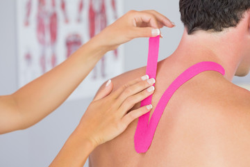 Physiotherapist putting on pink kinesio tape on male patients ne