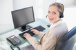 Smiling blonde call centre agent typing